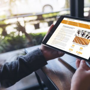 Mockup image of hands holding black tablet pc with white blank screen and laptop on wooden table background in cafe