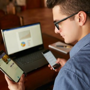 Attractive man in glasses working with multiple electronic internet devices. Freelancer businessman has laptop and smartphone in hands and laptop on table with charts on screen. Multitasking theme