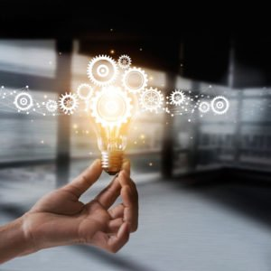 Hand holding light bulb and cog inside. Idea and imagination. Creative and inspiration. Innovation gears icon with network connection on metal texture background. Innovative technology in science and industrial concept
