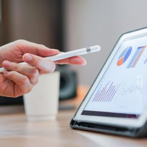 close up salesman employee hand using stylus pen to pointing on tablet screen to show company profit monthly in the meeting event at conference room , business strategy concept